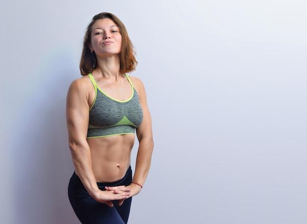 Slanke jonge fitness vrouw spieren in een grijze top zwarte legging geïsoleerd op een witte achtergrond.