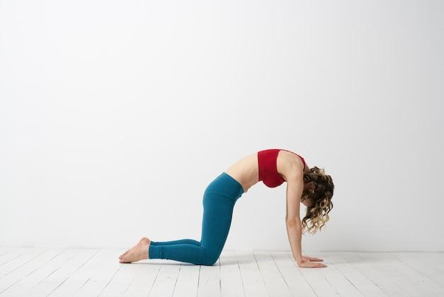 Slanke jonge vrouw beoefent yoga en oefeningen thuis in de studio