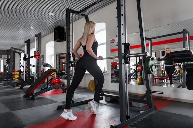 Slanke jonge vrouw blond in een stijlvol sport-t-shirt in zwarte legging in witte sneakers gaat over fitness in de sportschool.