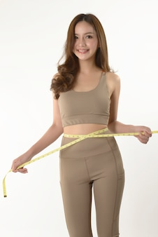 Slanke jonge vrouw die haar lichaam meet