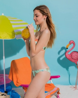 Slanke jonge vrouw die tropische cocktail drinkt