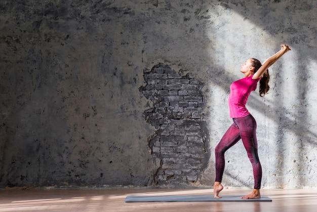 Slanke jonge vrouw die uitrekkende oefening tegen doorstane muur uitoefent