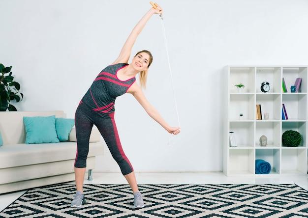 Slanke jonge vrouw die zich uitstrekt met haar springtouw staande in de woonkamer