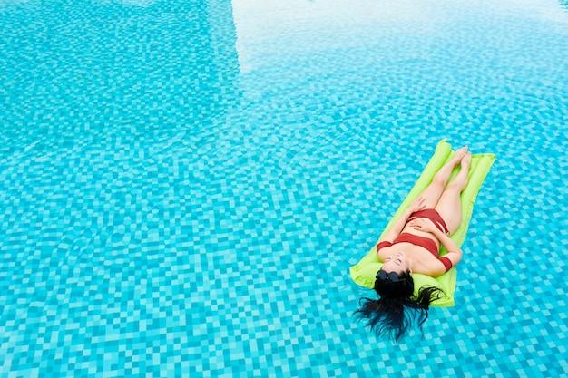 Slanke jonge vrouw in bikini zonnebaden op opblaasbare matras drijvend op het wateroppervlak in het zwembad