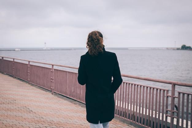 Slanke jonge vrouw in een zwarte jas loopt