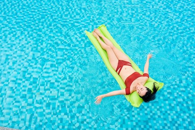 Slanke jonge vrouw in rode bikini ontspannen op opblaasbare matras drijvend in zwembad van kuuroord