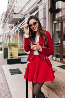 Slanke jonge vrouw in rode rok poseren met charmante glimlach op straat