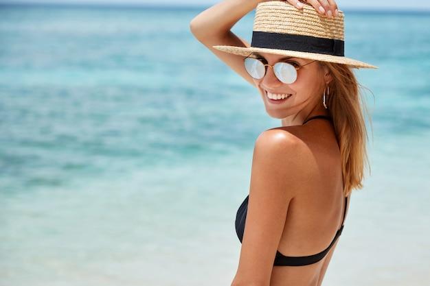 Slanke jonge vrouw in trendy tinten en hoed vormt aan de kust tegen blauw water, heeft een charmante glimlach op het gezicht, tevreden met een goed zomerverblijf. mooie fit vrouwelijke toerist alleen op zandstrand