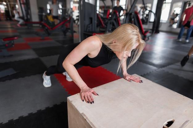 Slanke jonge vrouw in zwarte kleding doet push-ups op een houten kist in de sportschool
