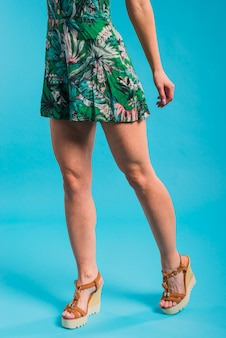 Slanke jonge vrouw poseren in bloemrijke jurk