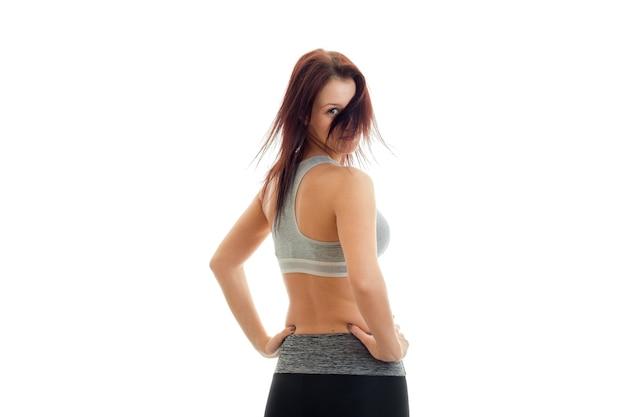 Slanke jonge vrouw staat met haar rug naar de camera, houdt je handen aan de zijkanten van haar haar en gesloten gezicht geïsoleerd op een witte muur