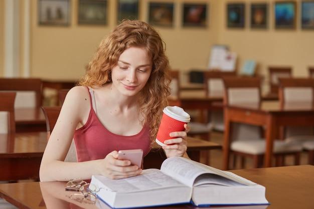 Slanke knappe jonge student zit in de lokale bibliotheek, houdt een kopje koffie en smartphone, kijkt naar het mobiele scherm, bekijkt video's, heeft pauze tijdens zijn studie. studentenleven concept.