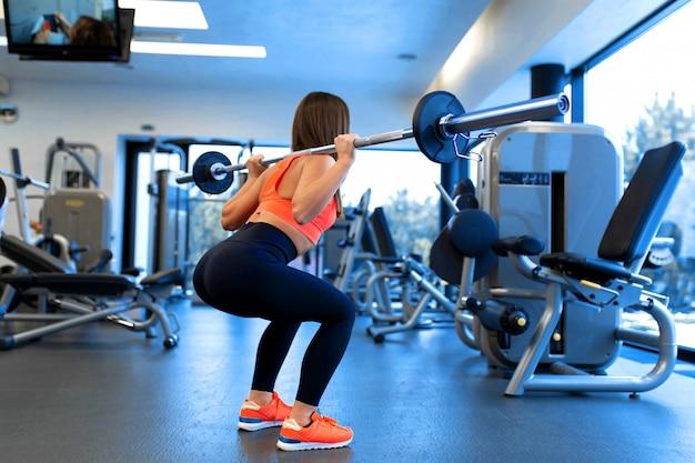 Slanke knappe jonge vrouw in sportkleding squats met een halter op de schouder in de sportschool