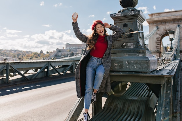 Slanke lachende vrouw in vintage jeans poseren op het platform achtergrond in zonnige dag in parijs