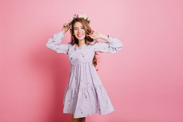 Slanke lieve vrouw in paarse jurk met plezier in de studio