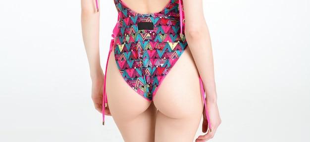 Slanke magere vrouw billen lichaam poseren in roze gedrukte zwembroek geïsoleerd op witte studio