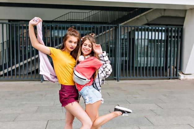 Slanke meisjes in schattige denim shorts dansen voor ijzeren hek en glimlachend genieten van weekend