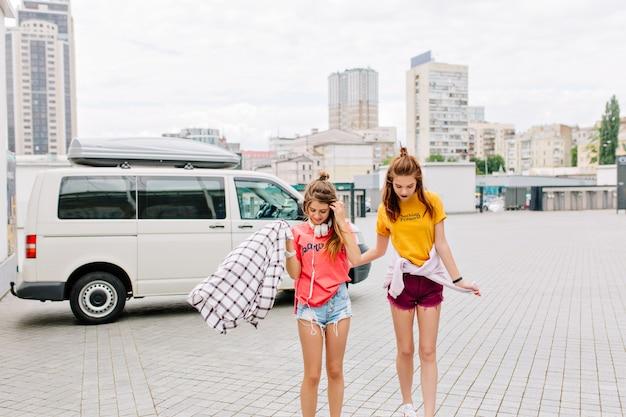 Slanke meisjes met lange benen die naar beneden kijken, staande op het stadsplein met wolkenkrabbers