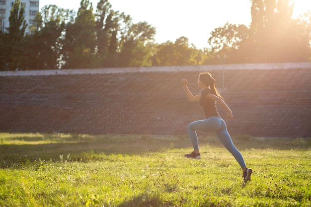 Slanke modelatleet in sportkleding die tijdens de training springt. ruimte voor tekst