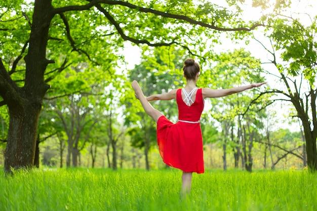 Slanke mooie brunette meisje in een rode jurk voert yoga houdingen uit in een zomer park. groen bos bij zonsondergang