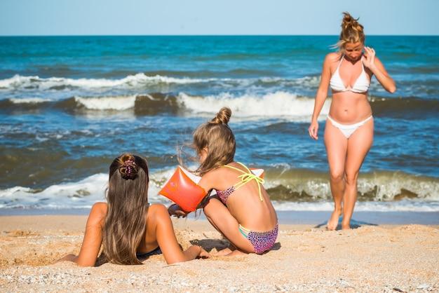Slanke mooie jonge vrouw en twee mooie kleine dochters genieten van een vakantie op een zandstrand