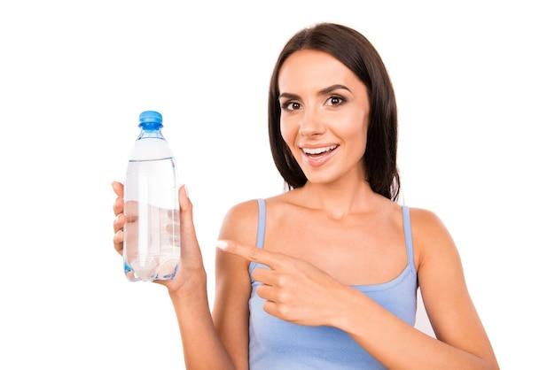 Slanke mooie vrouw die een fles met water toont