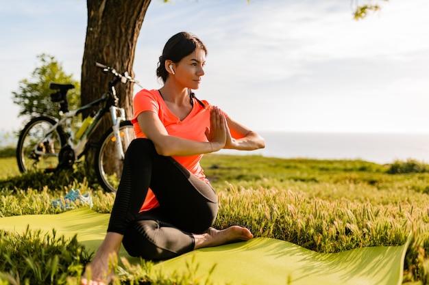 Slanke mooie vrouw die sporten in ochtend in park doet die yoga doet