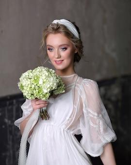 Slanke mooie vrouw in een luxe trouwjurk in de studio. portret van de bruid met een wit boeket in haar handen.