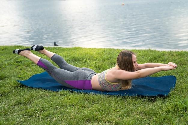 Slanke mooie vrouw in sport kleding praktijken yoga houdingen op de mat naast een meer op een zonnige zomerdag, outdoor fitness. concept van een gezonde levensstijl