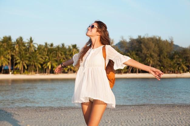 Slanke mooie vrouw in witte jurk op tropisch strand op zonsondergang lederen rugzak te houden.