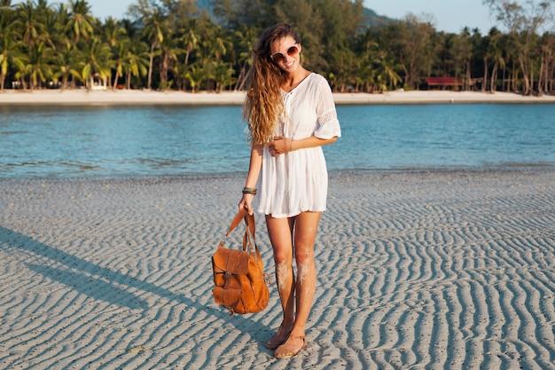 Slanke mooie vrouw in witte katoenen jurk wandelen op tropisch strand op zonsondergang lederen rugzak te houden.