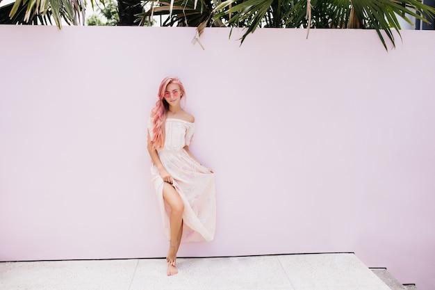 Slanke mooie vrouw met lang roze haar met een zachte glimlach.