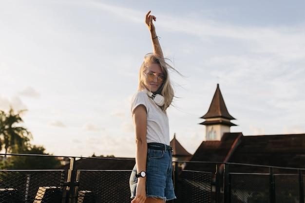 Slanke mooie vrouw plezier buiten in de avond. blij blonde vrouw in hoofdtelefoons en denim shorts poseren op hemelachtergrond.