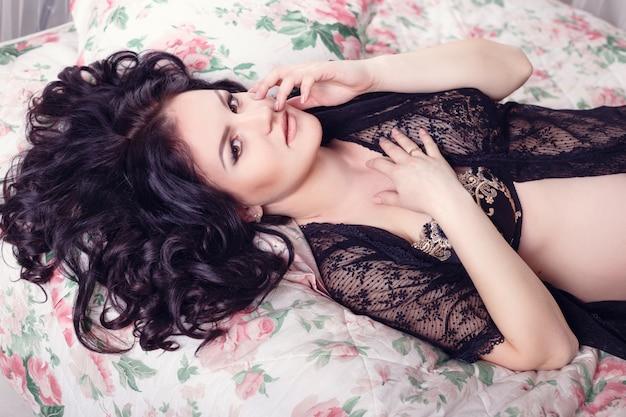 Slanke mooie zwangere vrouw zittend op het bed in de slaapkamer. prachtige lingerie. stijlvolle en sexy zwangerschap.