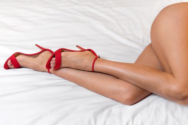 Slanke perfecte vrouwenbenen in rode hoge hielsandals, die op het bed liggen.