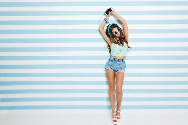 Slanke schattige jonge dame thuis chillen, favoriete liedje luisteren en dansen met een blije glimlach. portret van schitterend meisje in zonnebril met lange gebruinde benen die pret op gestreepte muur hebben.