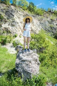 Slanke sexy jonge vrouw poseren in de buurt van grote steen en groen hoog gras, perfect zomeravontuur