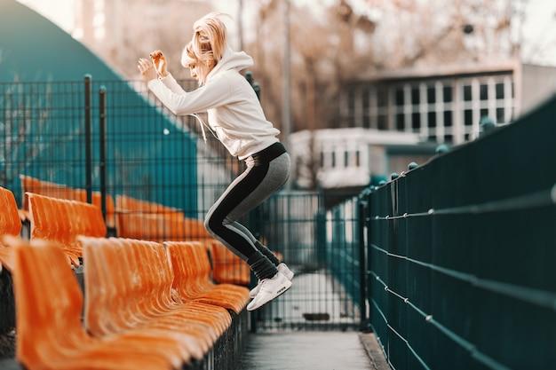 Slanke sportieve blonde vrouw in sportkleding springen op de stoel