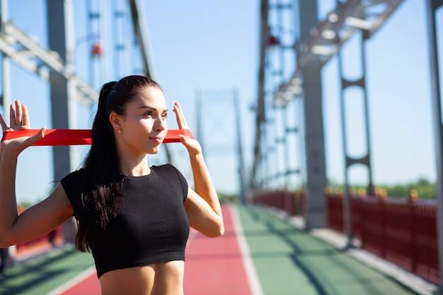 Slanke sportieve vrouw doet training met rubberen weerstandsband op een brug. ruimte voor tekst