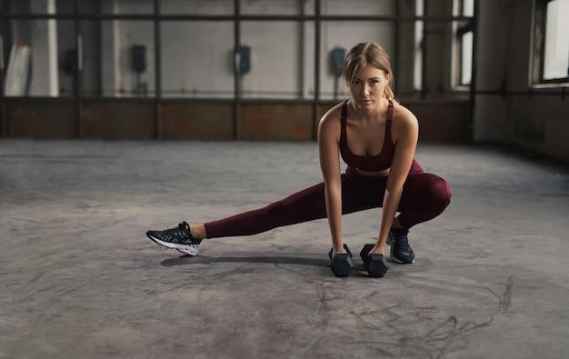 Slanke sportvrouw van het volledige lichaam kant lunge met halters doen tijdens fitnesstraining in ruime sportschool