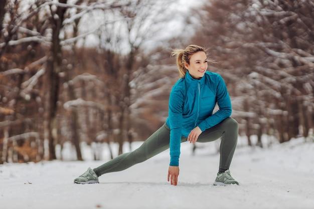Slanke sportvrouw warming-up oefeningen in de natuur op sneeuwweer. koude temperatuur, wintersport, gezond leven, winter