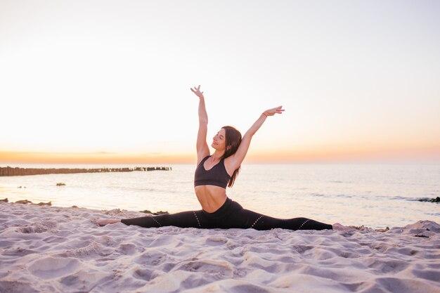 Slanke sterke jonge vrouw in het zwart beoefenen van yoga de splitsingen doen op zand strand close-up met kopie ruimte. zonsondergang, zomer. healhy lifestyle concept.