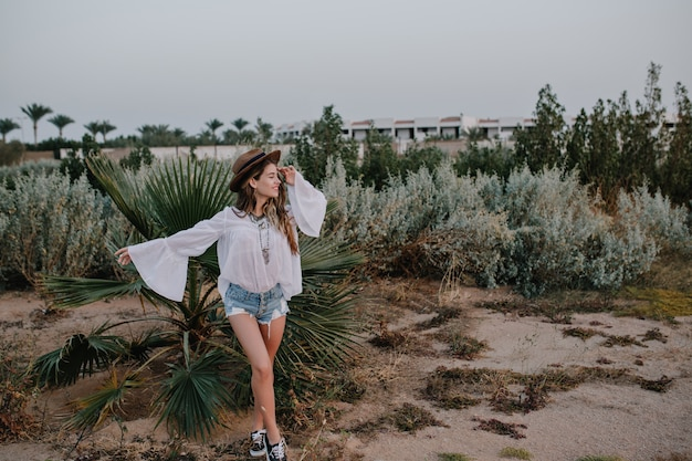 Slanke stijlvolle vrouw in witte blouse en denim shorts buiten wandelen geniet van uitzicht op exotische planten en mooie lucht. aantrekkelijke jonge vrouw in sportieve schoenen die graag met dromerige gezichtsuitdrukking stellen