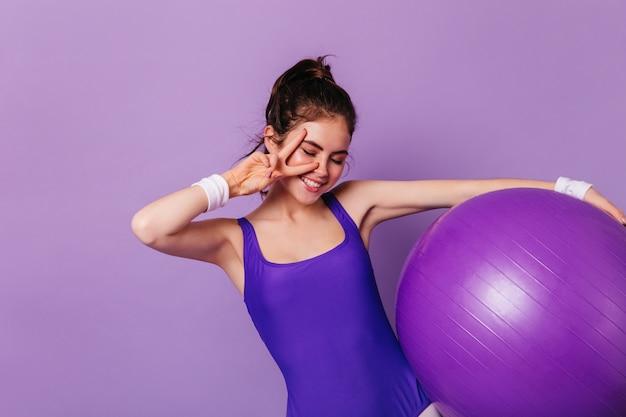 Slanke turnervrouw houdt fitball vast en toont vredesteken op paarse muur