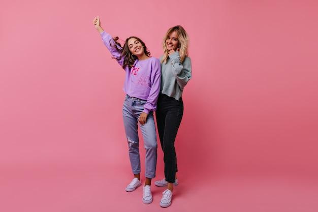 Slanke, vrolijke meisjes die lachen tijdens studioportretshoot. indoor portret van emotionele vriendinnen geïsoleerd op rooskleurig.
