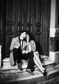 Slanke vrouw die de jonge gelukkige mens kussen en dichtbij deur op straat zitten