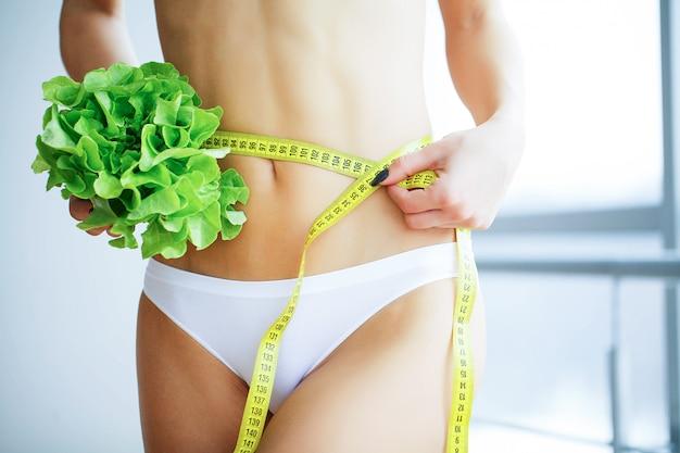 Slanke vrouw die in handen verse groene salade.