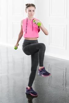 Slanke vrouw die oefening met groene domoren doet