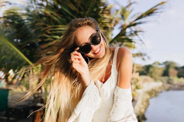Slanke vrouw die op exotische plaats geniet. blije gelooide dame die zich dichtbij palmbomen bevindt en glimlacht.
