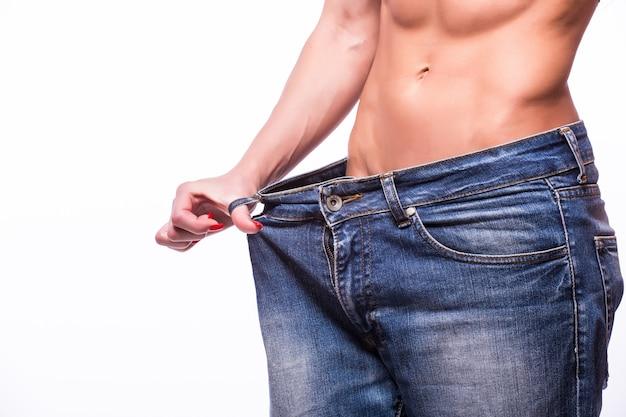 Slanke vrouw die oversized jeans trekt. gewichtsverlies concept. geïsoleerd op een witte muur